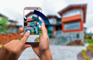 Hands Holding Phone in Front of House with Smart Home Installation Services in Plantation